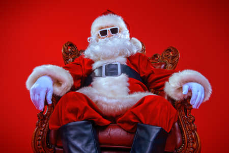 Cool modern Santa Claus in sunglasses over red background. Christmas concept. Reklamní fotografie - 87774867