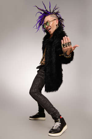 Full length portrait of a punk rock musician posing at studio. Youth alternative culture. 免版税图像