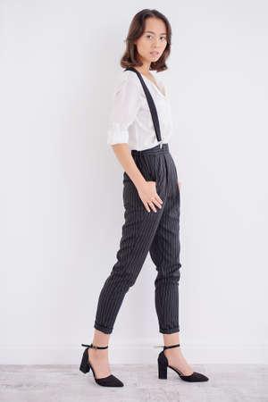 De jonge Aziatische vrouw kleedde zich in wit overhemd en klassieke broeken die bij studio stellen. Zakelijke stijl in kleding. Mode schot.