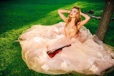 Beautiful fairy girl playing the violin on a sunny glade in the park. Musical concept. Classical music, violin. Фото со стока