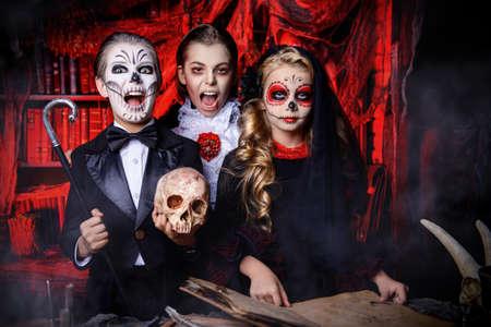Halloween feest. Vrolijke kinderen in carnavalskostuums vieren Halloween in het landschap van het hol van de heks. Stockfoto