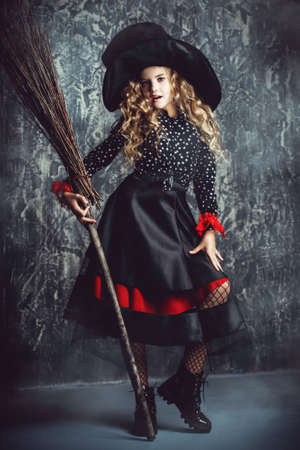 Beautiful child girl in a costume of a witch over grunge background. Halloween party. Stock Photo