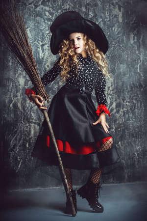 Muchacha niño hermosa en un traje de una bruja sobre fondo del grunge. fiesta de halloween . Foto de archivo - 87870698