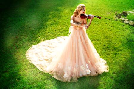 美しい妖精の女の子が公園で日当たりの良い空き地でバイオリンの演奏します。音楽的な概念。クラシック音楽、バイオリン.
