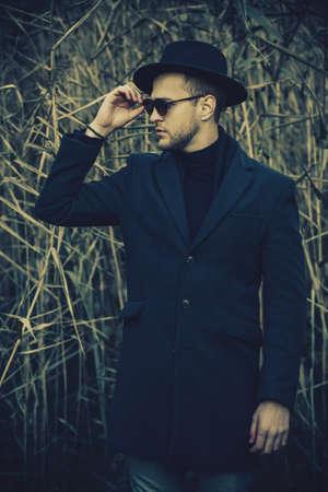 Hiver de l & # 39 ; automne de l & # 39 ; automne mignon bel homme vêtu d & # 39 ; un manteau noir et un chapeau marchant dans le parc de l Banque d'images - 88049703