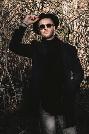 Seasonal autumn fashion. Elegant handsome man wearing a black coat and a hat walking in the autumn park. Stock Photo