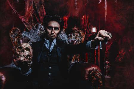 Halloween. Un homme effrayant et sombre, vêtu d'un manteau noir, est assis dans un fauteuil avec un crâne dans un vieux château abandonné. Le Seigneur des Ténèbres. Homme vampire. Banque d'images - 88049972