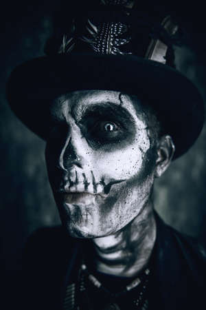 Close-up portrait of a man with a skull makeup dressed in a tail-coat and a top-hat. Baron Saturday. Baron Samedi. Dia de los muertos. Day of The Dead. Halloween. Stock Photo - 88071337