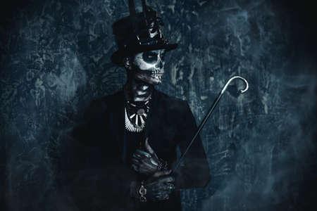 Een man met een schedelmake-up gekleed in een staartjas en een hoge hoed. Baron zaterdag. Baron Samedi. Dia de los muertos. Dag van de Doden. Halloween. Stockfoto - 88071345