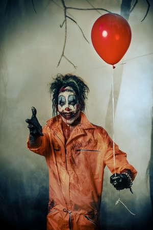 Pagliaccio spaventoso macchiato di sangue in una foresta di notte con un palloncino. Pagliaccio zombie maschio. Halloween. Orrore. Archivio Fotografico - 88071348