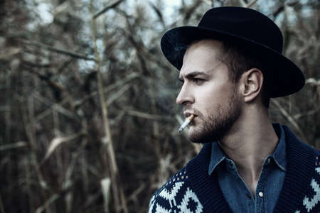 Close-up portrait of a handsome brutal man in cardigan and a hat smoking a cigarette outdoor over autumn nature background. Autumn fashion. Male fashion. Stock Photo - 88087751