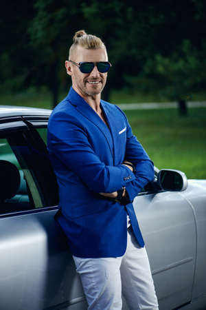 Modern mature man standing by his car. Business style. Vehicle concept. Luxury.