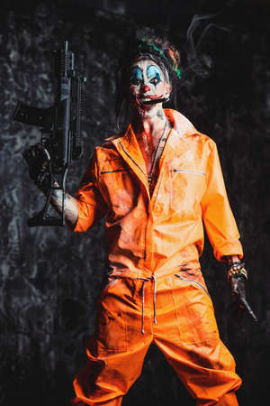 Crazy evil clown man stained in blood is smoking a cigar and holding a gun. Halloween. Horror, thriller film. Stock Photo