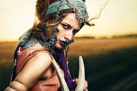 Magnificent gypsy fortune teller with a skull in the rays of the sunset. Stock Photo