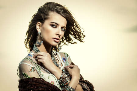 Bohemian style. Portrait of a beautiful sensual woman over sky background. Beauty, fashion. Jewelry.