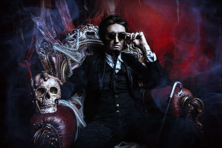 Halloween. Frightening gloomy man in a black tailcoat sits in an armchair with a skull in an old abandoned castle. The Dark Lord. Vampire man. Reklamní fotografie - 88190633