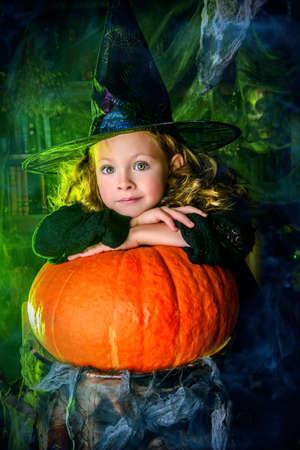 Fröhliches Halloween. Nettes Kindermädchen im Hexekostüm ist im Versteck einer Hexe mit Kürbis. Standard-Bild - 88190634