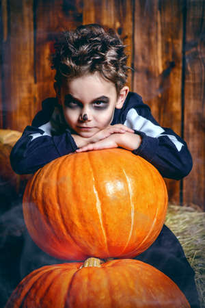 Portrait of a cute boy in a costume of skeleton sitting with pumpkin on a hay. Happy Halloween! Stock Photo