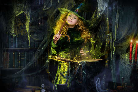 Happy Halloween. Cute child girl in witch costume is in a witchs lair. Cute cheerful little witch cooks a magic potion.