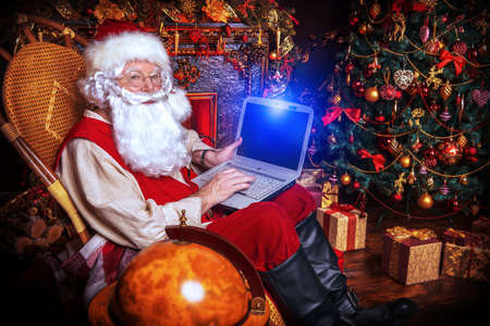 Traditional Santa Claus at his house surfing in the Internet with his laptop. Christmas time. Christmas decoration. Stock Photo