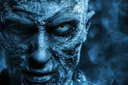 Close-up portrait of a zombie man covered with snow. Halloween. Horror film.
