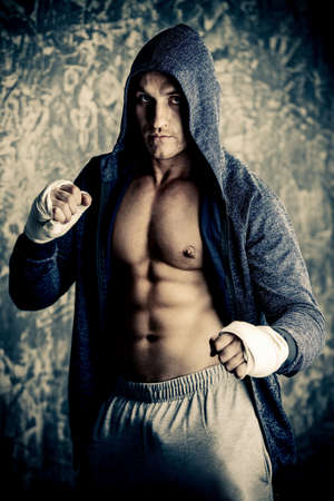 Handsome athletic man in hoodie stands by a grunge wall. Boxer, street fighter.