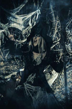 De kwade heks roept in het struikgewas van het bos op. Sprookjes op Halloween. Stockfoto