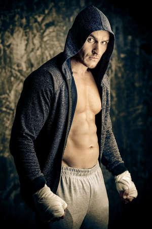 Bel homme athlétique en capuche se tient près d'un mur de grunge. Boxer, combattant de rue. Banque d'images - 88368161