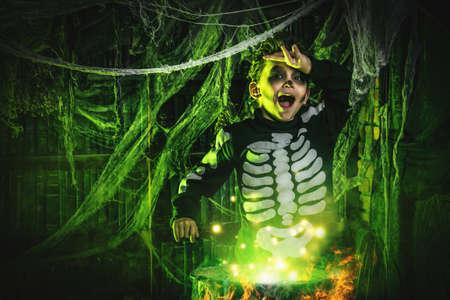 해피 할로윈. 재미 있은 자식 소년 해골의 의상에서 마법의 묘약 마녀의 은신처에 요리.