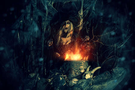The old witch cooks a sorcery potion in the thicket of the forest. Fairy tales on Halloween. Stock Photo