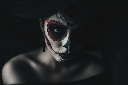 Portrait of a girl with sugar skull makeup over black background. Calavera Catrina. Dia de los muertos. Day of The Dead. Halloween. Imagens - 88368265