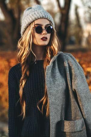 Moda outono sazonal. Jovem mulher moderna que veste a roupa morna elegante que levanta no parque do outono.