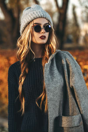 Seasonal autumn fashion. Modern young woman wearing fashionable warm clothes posing in the autumn park. Archivio Fotografico