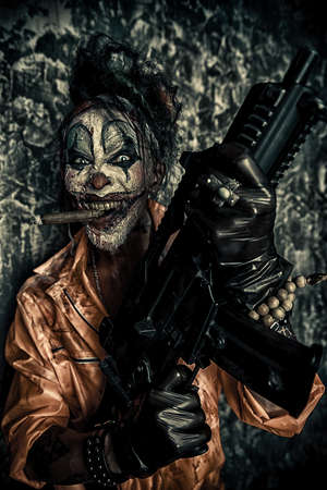 Crazy evil clown man stained in blood is smoking a cigar and holding a gun. Halloween. Horror, thriller film. Stock Photo - 88555051