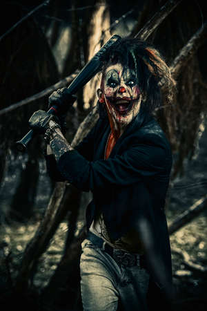 Scary punk clown man smeared with blood in a night forest. Halloween. Horror, thriller film. Stock Photo - 88555054