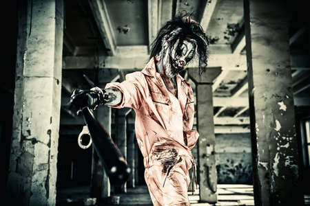 Sinister clown man stained in blood is standing in an abandoned house. Male zombie clown. Halloween. Horror.