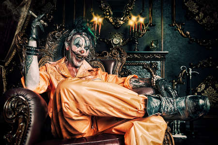 Evil clown man stained in blood is sitting with cigar in a room with vintage interior. Halloween. Horror, thriller film.