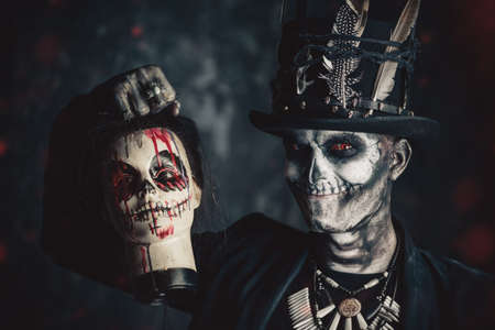 A man with a skull makeup dressed in a tail-coat and a top-hat. Baron Saturday. Baron Samedi. Dia de los muertos. Day of The Dead. Halloween. Stock Photo - 88802397
