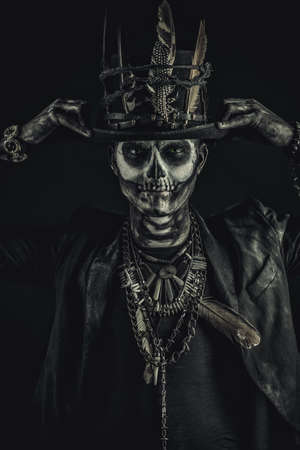 A man with a skull makeup dressed in a tail-coat and a top-hat. Baron Saturday. Baron Samedi. Dia de los muertos. Day of The Dead. Halloween.
