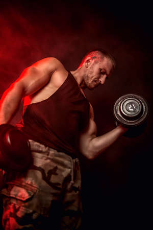 Muscular brutal man doing exercises with dumbbells. Health and sports concept. Military style. Banco de Imagens
