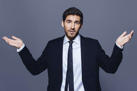 Emotional businessman pulls his hands apart, expressing surprise and disappointment. Business concept. Фото со стока