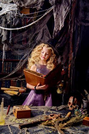 Schöne charmante kleine Hexe zaubert in ihrem Versteck. Halloween. Standard-Bild - 88925443