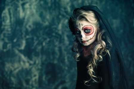 Portrait of a child girl in a costume of Calavera Catrina over dark grunge background. Little girl with sugar skull makeup. Halloween party. Dia de los muertos. Day of The Dead. 写真素材