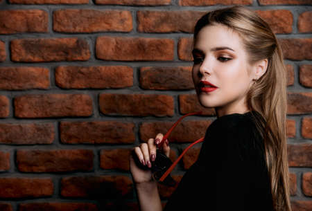 Pretty girl in black dress posing by the brick wall. Modern youth fashion. Stock Photo