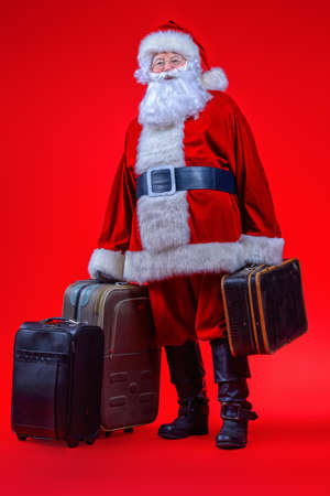 Christmas, tourist trip concept. Santa Claus with suitcases is going to travel around the planet. Christmas time. Time for miracles. Copy space.