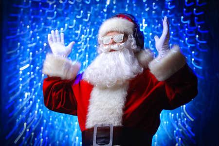 雪のメガネとヘッドフォンで DJ サンタクロース。クリスマスの歌と音楽。ディスコはバックグラウンドで点灯します。 写真素材