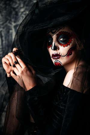 Retrato de un Calavera hermoso y asustadizo Catrina en vestido negro y sombrero negro con un velo sobre fondo oscuro. Maquillaje del cráneo del azúcar. Dia de los muertos. Dia de los Muertos. Víspera de Todos los Santos. Foto de archivo - 88907281