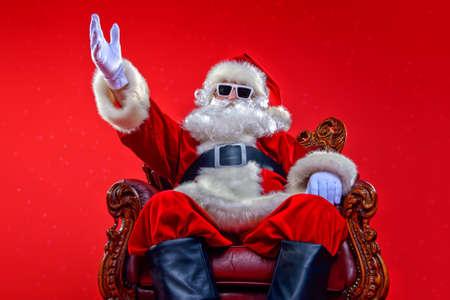 赤い背景の上にサングラスでクールな現代のサンタクロース。クリスマスのコンセプト。