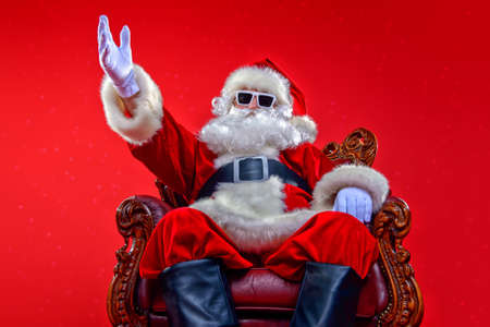 Cool modern Santa Claus in sunglasses over red background. Christmas concept. Фото со стока - 89263583