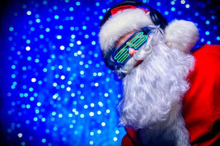 DJ 산타 클로스 빛나는 안경 및 헤드폰. 크리스마스 노래와 음악. 백그라운드에서 디스코 조명입니다.